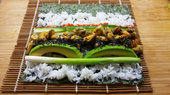 Muscheln, Avocado, Frühlingszwiebel und Gurke auf dem Noriblatt verteilt