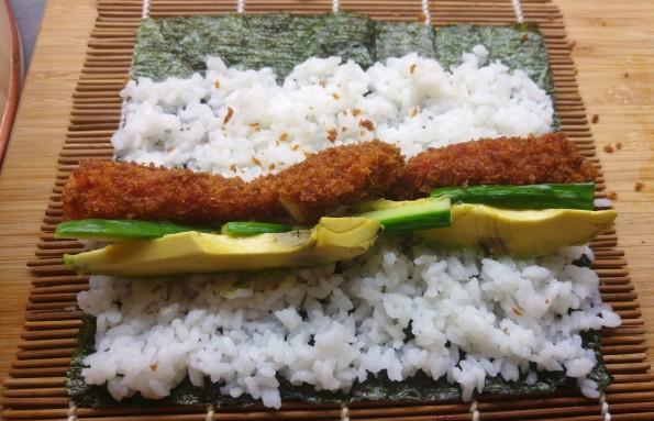Sushirolle belegen mit frittierter Garnele, Avocado und Gurke