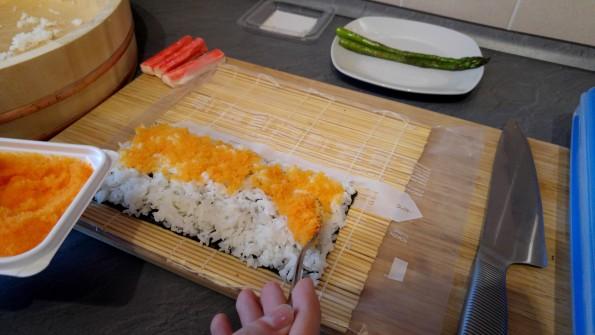 Masago auf dem Reis verteilen