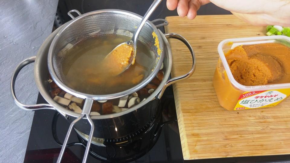 Miso Paste mit Hilfe eines Siebs in der Suppe verrühren