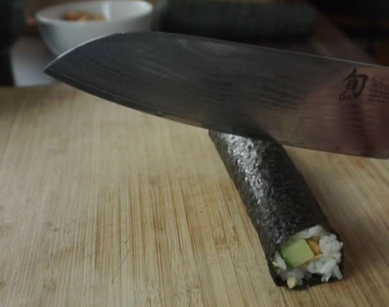 Hoso Maki Sushi mit einem scharfen Messer schneiden