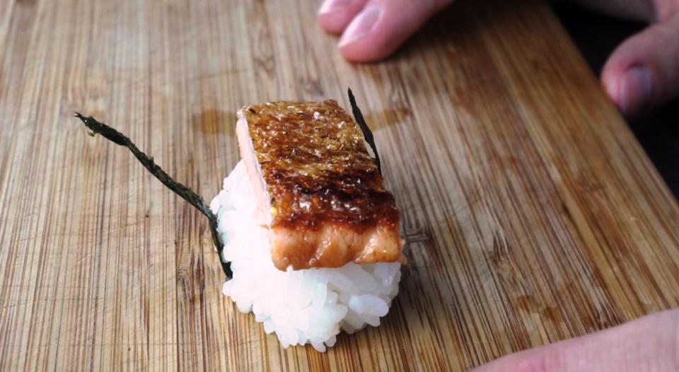 Nigiri Sushi mit Streifen von Norialge sichern